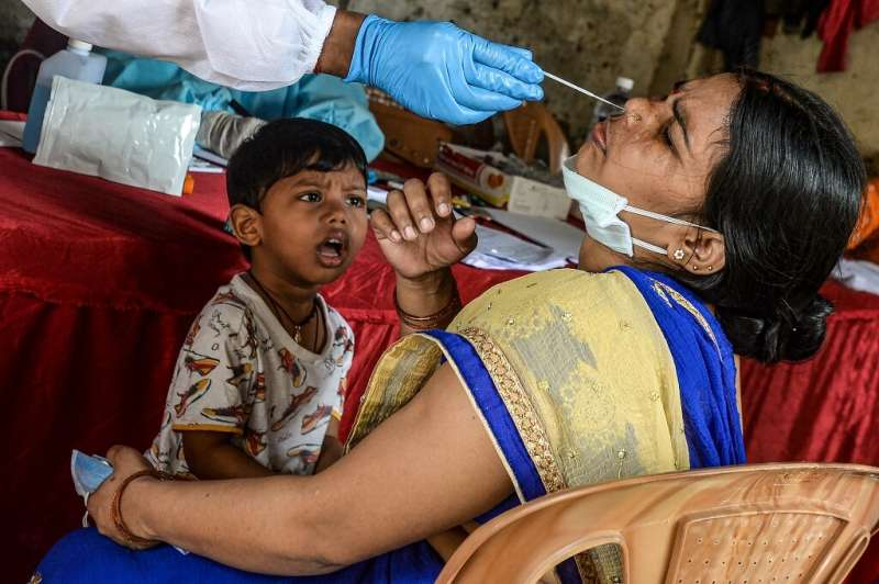 A child looks on as his mother is tested for coronavirus in Mumbai