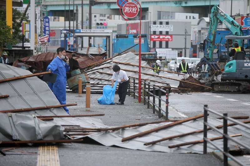A clean-up crew works to remove roofs that  were blown off into a Fukuoka street by Typhoon Haishen
