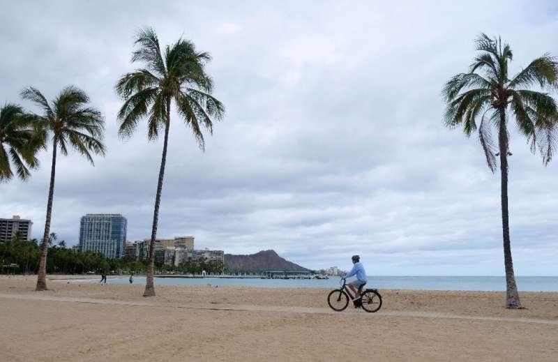A cyclist rides along an empty Waikiki Beach in Honolulu, Hawaii as Hurricane Douglas veers northward, sparing Oahu from a direc