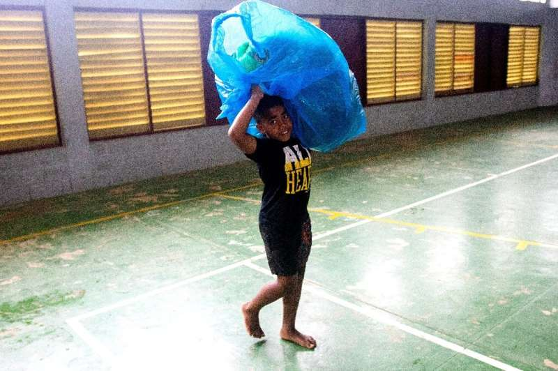 A Fijian boy carries a bag to a temporary shelter to avoid strong damaging winds from super cyclone Yasa in the capital city of
