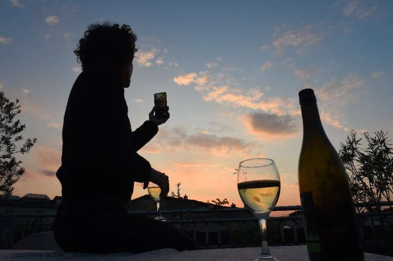 A French woman under lockdown raises a glass of wine with friends via a video call