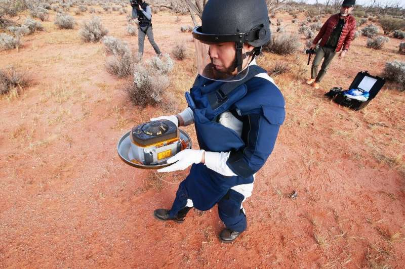 A JAXA scientist holds the capsule with samples collected from a distant asteroid that were recovered in the South Australia des