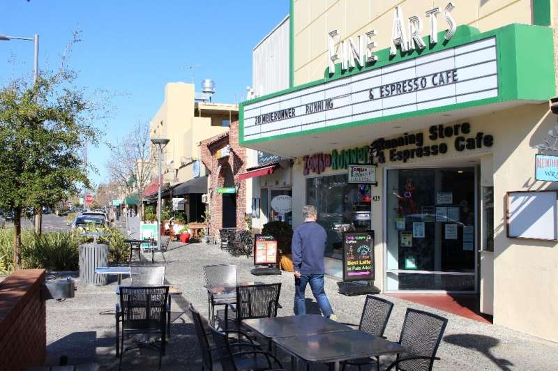 A man glances into ZombieRunner coffee shop as he strides along a quiet sidewalk in downtown Palo Alto, which is largely deserte