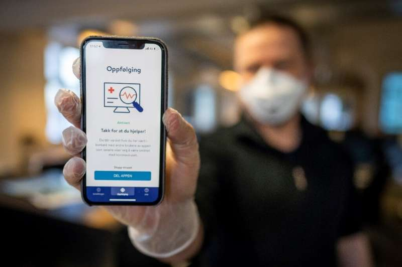 A man holds a smartphone showing a tracking and tracing app launched by the National Institute of Public Health to try to halt a