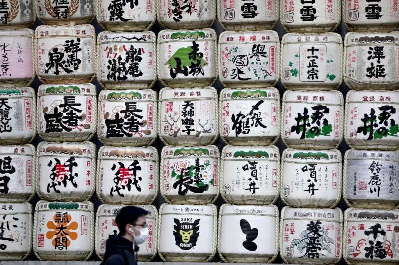 A man in a facemask walks past barrels of sake at the entrance to Meiji shrine in Tokyo