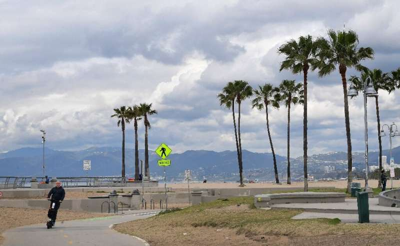 A man rides a scooter along a bike path near Venice Beach in Los Angeles on March 20, 2020, a day after Los Angeles County annou