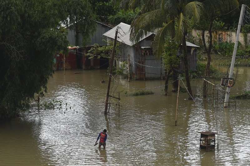 A man wades through a flooded village in in Bangladesh, where a third of the country is underwater