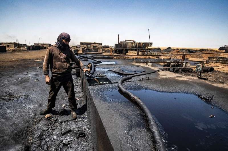A man works at a makeshift refinery distilling crude oil in the village of Bishiriya in the countryside near Al-Qahtaniya in nor