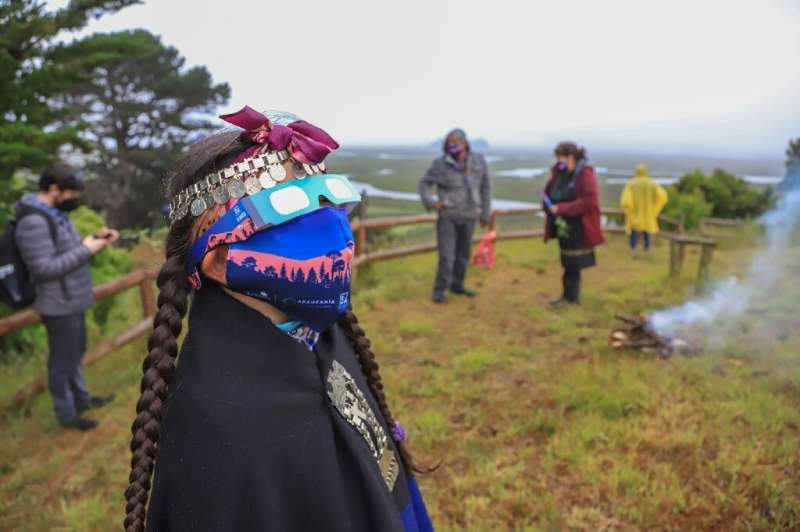 A Mapuche indigenous family watch the total solar eclipse in Carahue, Araucania region in southern Chile