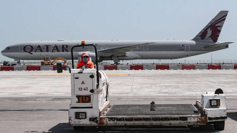 A masked worker drives a loader in front of a Qatar Airways jet at Doha's Hamad International airport