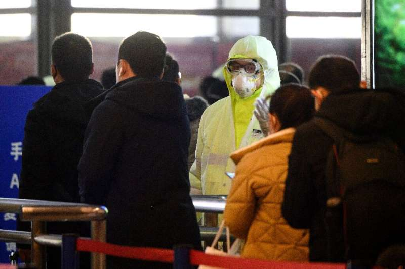 A medical worker wearing protective clothing monitors rail passengers arriving in Shanghai