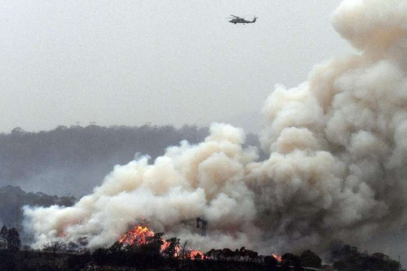 A military helicopter flies above a burning woodchip mill in Australia's New South Wales state