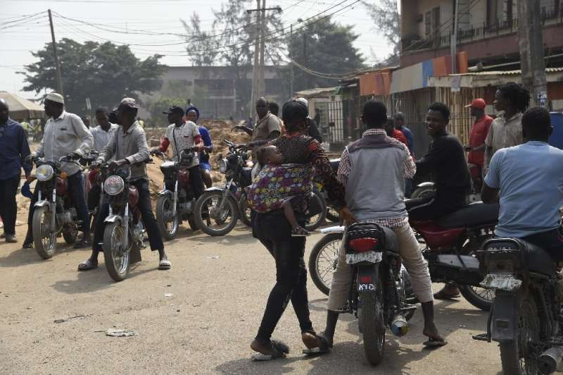 A mother and her baby try to get a ride from a motorbike taxi parked on a street in Lagos