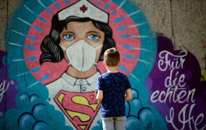 A mural painted by artist Kai 'Uzey' Wohlgemuth featuring a nurse as Superwoman on a wall in Hamm,  Germany