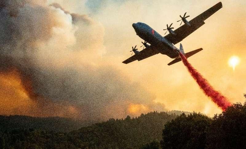 An aircraft drops fire retardant on a ridge during the Walbridge fire, part of the larger LNU Lightning Complex fire, as flames