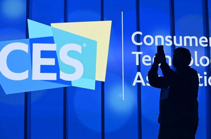 An attendee photographs a sign next to the CES logo ahead of the first keynote address at the 2020 Consumer Electronics Show  in