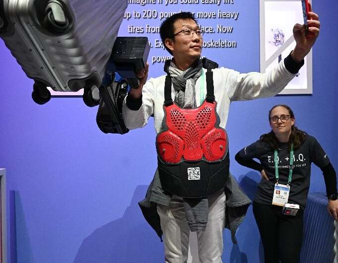 An attendee takes a selfie as he lifts a 22.7 kg suitcase with the help of the Sarcos Guardian XO exoskeleton arm at the 2020 Co