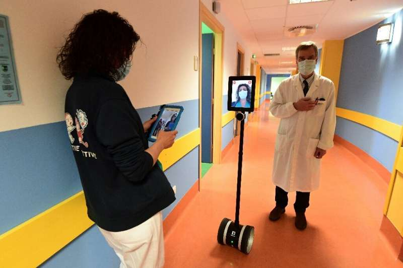 A nurse (L) manipulates a robot called Ivo used to help patients infected by the novel coronavirus at the Circolo di Varese hosp