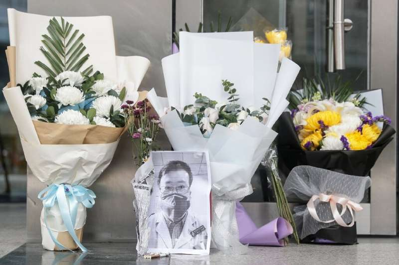 A photo of the late Doctor Li Wenliang is seen with flower bouquets at a hospital in Wuhan