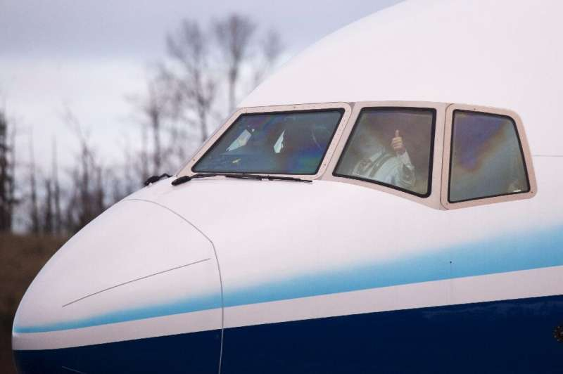 A pilot gives a thumbs up as he taxis a Boeing 777X airplane before taking off on its inaugural flight at Paine Field in Everett