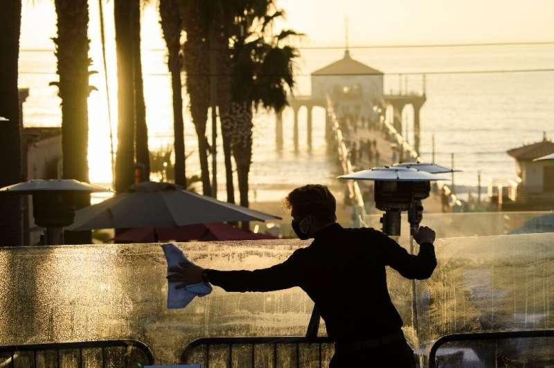 A restaurant employee cleans a plexiglass table divider while preparing for outdoor dining service in Manhattan Beach, Californi
