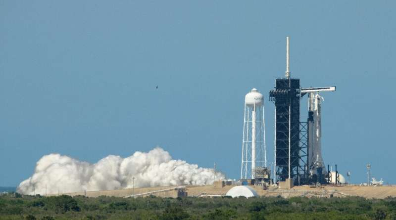 A SpaceX Falcon 9 rocket with the company's Crew Dragon spacecraft onboard at Launch Pad 39A during a brief static fire test on