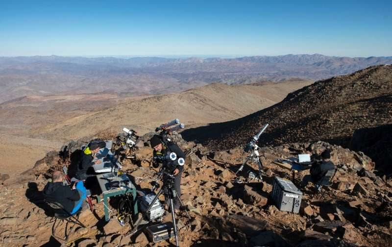 Asronomers preparing telescopes to observe the total eclipse of the sun from the Silla Observatory in the Atacama desert in July