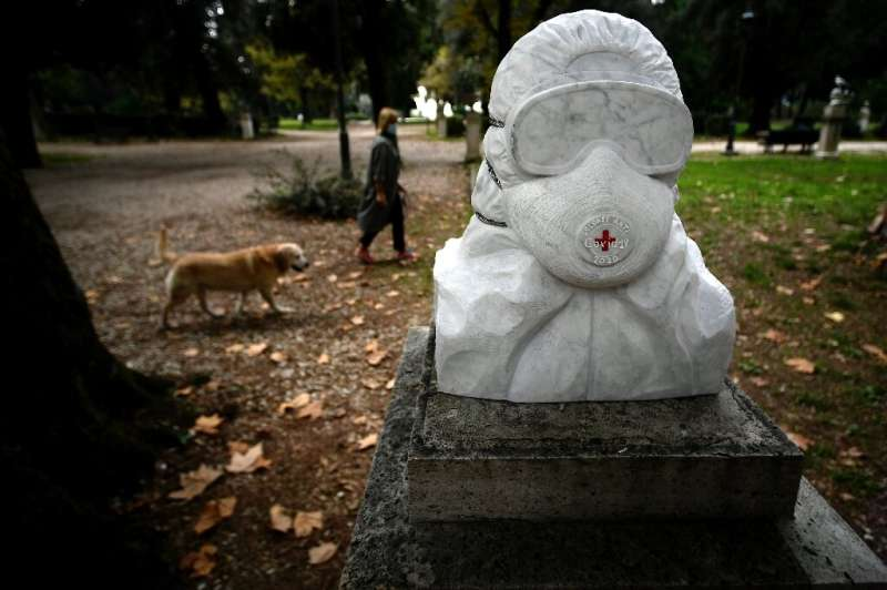 A woman walks her dog past a marble bust dedicated to doctors, nurses and health workers in Rome's Pincio Park as Italians and m
