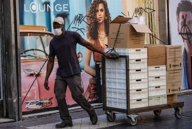 A worker wears a face mask as a precautionary measure against the spread of the new coronavirus as he pulls a cart with boxes ne
