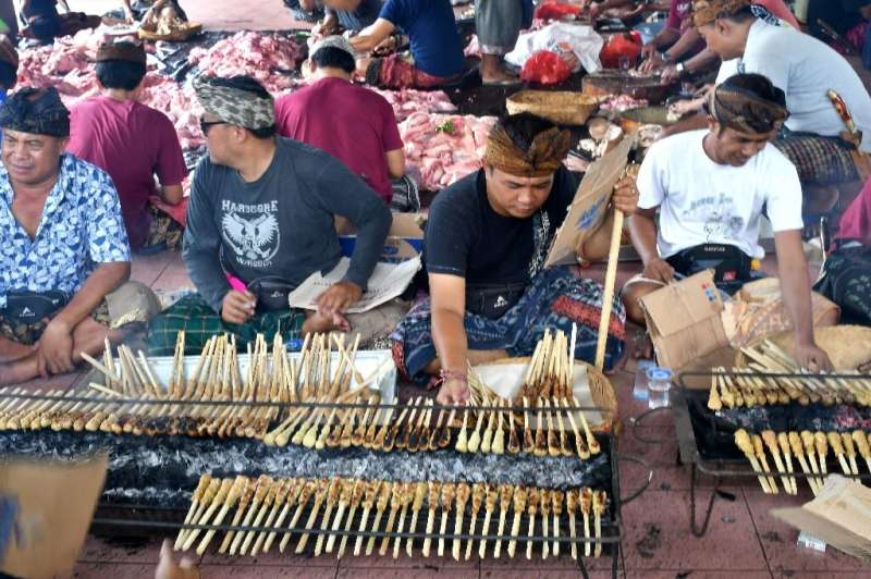 Balinese men preparing pork sate for a traditional wedding on Indonesia's resort island of Bali. Hundreds of pigs have died from