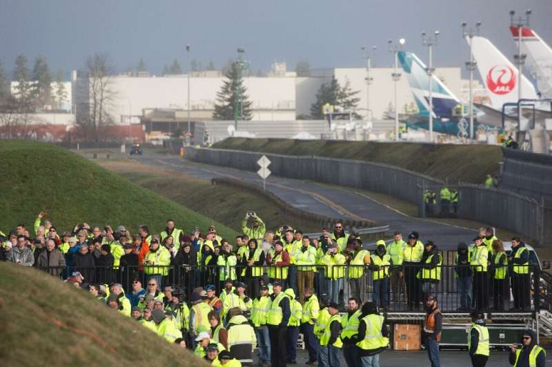 Boeing employees and others watch as a Boeing 777X airplane taxis before taking off on its inaugural flight at Paine Field in Ev