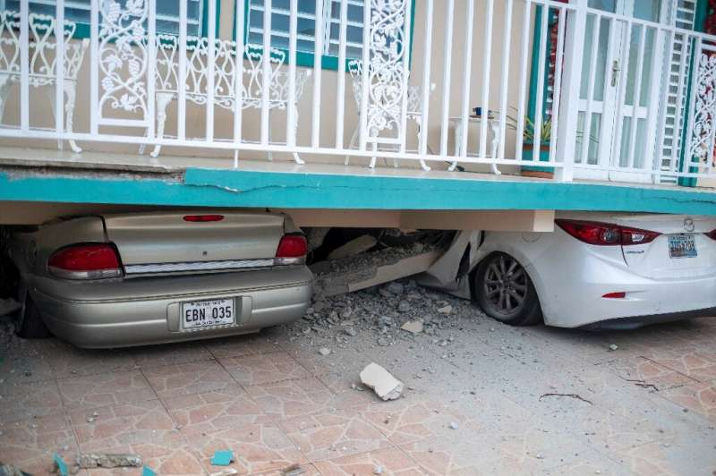 Cars are seen under a collapsed house damaged by an earthquake in Guanica, Puerto Rico on January 6