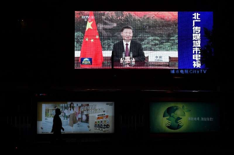 Chinese President Xi Jinping appears on an outdoor screen in Beijing as he speaks by video link at the United Nations General As