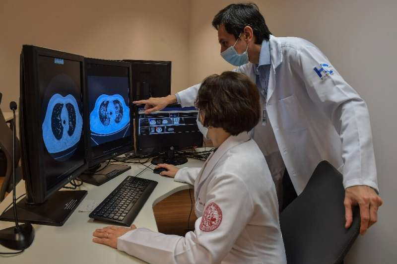 Claudia Leite (L) and Marcio Sawamura of the University of Sao Paulo Clinical Hospital look at tomography images of lungs