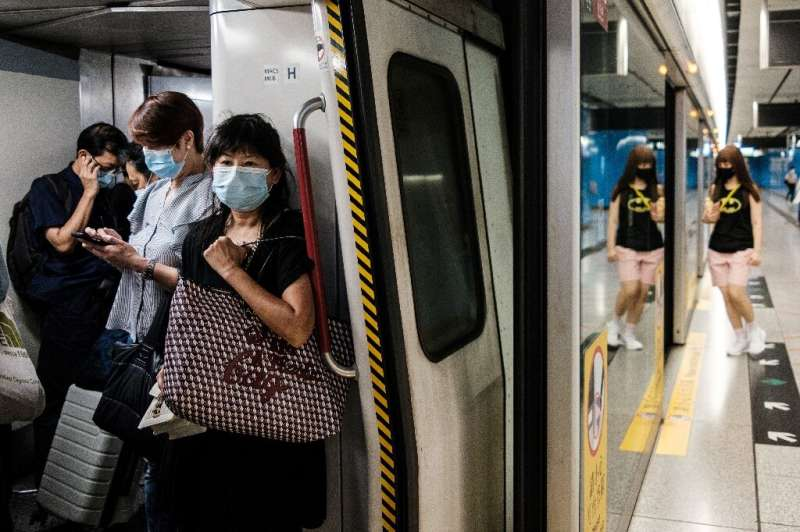 "Commuters wear face masks on a metro train in Hong Kong. The city's leader says coronavirus is running ""out of control&quot"