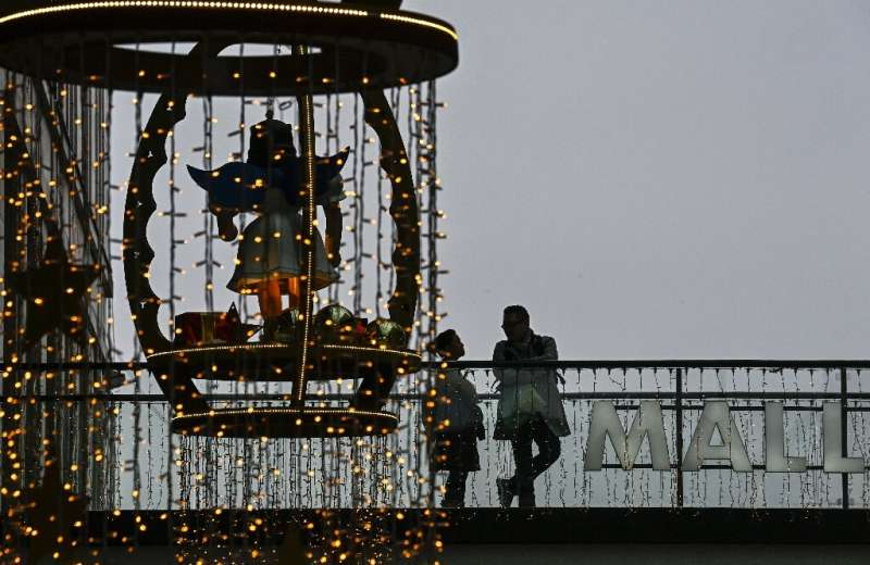 Customers stand on a balcony next to Christmas decorations in a shopping mall in Berlin. Germany plans to ease virus curbs for C
