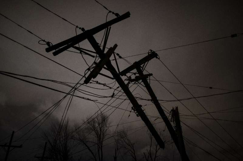 Damaged utility poles and lines hang above a street on March 3 in Nashville