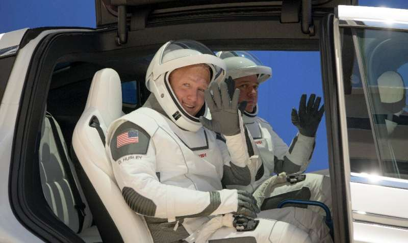 Douglas Hurley, left, and Robert Behnken, wearing SpaceX spacesuits, are seen as they depart for Launch Pad 39A on May 23, 2020