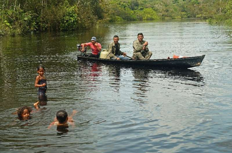 Fishermen and children are seen in the river in Bauana, a village in the heart of the Brazilian Amazon, on March 14