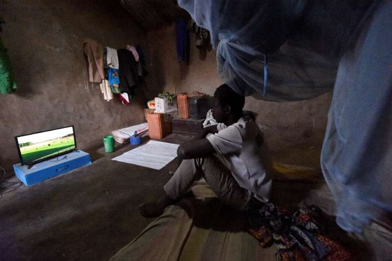 Footy night: Ousmane Kantcho settles down to watch an English Premier League match, thanks to solar energy