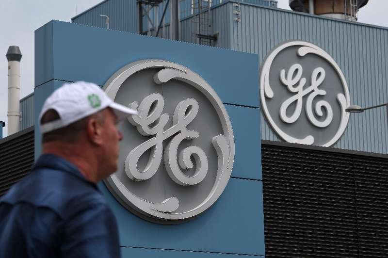 General Electric reported higher first-quarter profits on a gain from a divestiture, but warned that the current quarter would s