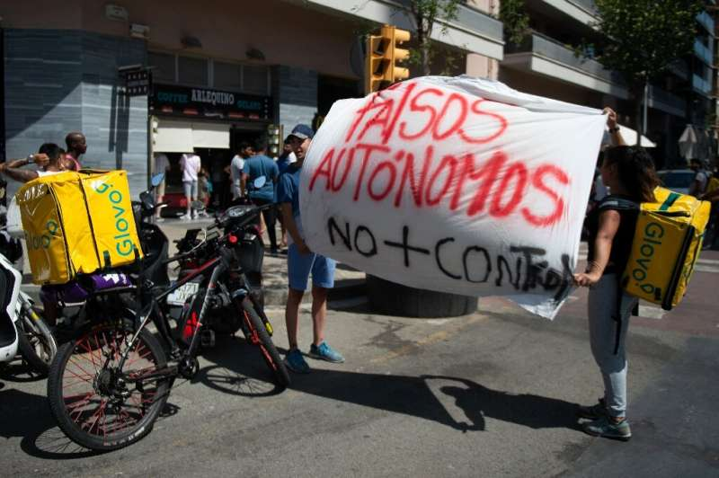 Glovo riders hold a banner reading 'Fake self-employed, no more control' during a strike in August 2019