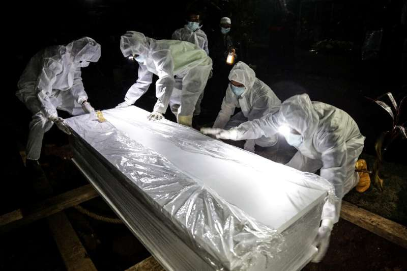 Graveyard workers in full prtective gear move a coffin in Bogor, Indonesia