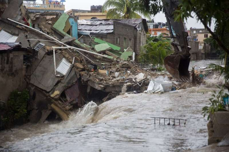 Houses collapsed after floodwaters ran through the streets of Santo Domingo as Tropical Storm Laura batters the region