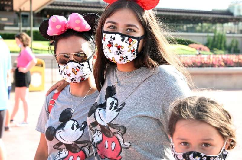 In hard-hit Florida the Walt Disney World theme park partially reopened after four months of shutdown, with some visitors combin