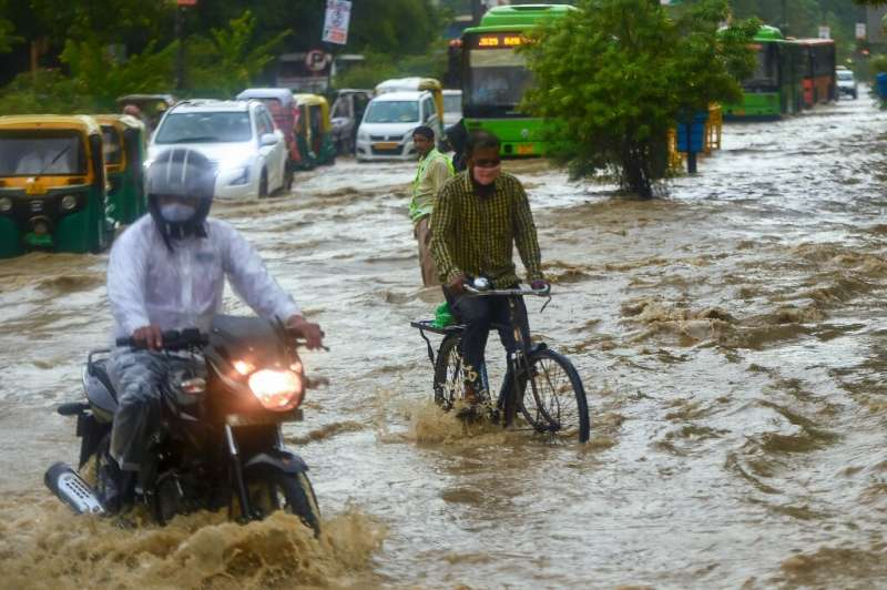 In New Delhi, commuters battled through knee-deep waters