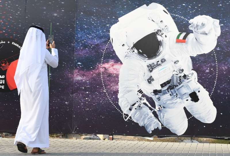 In photo taken on September 25, 2019 a man takes a picture of an illustration depicting an astronaut with the Emirati national f