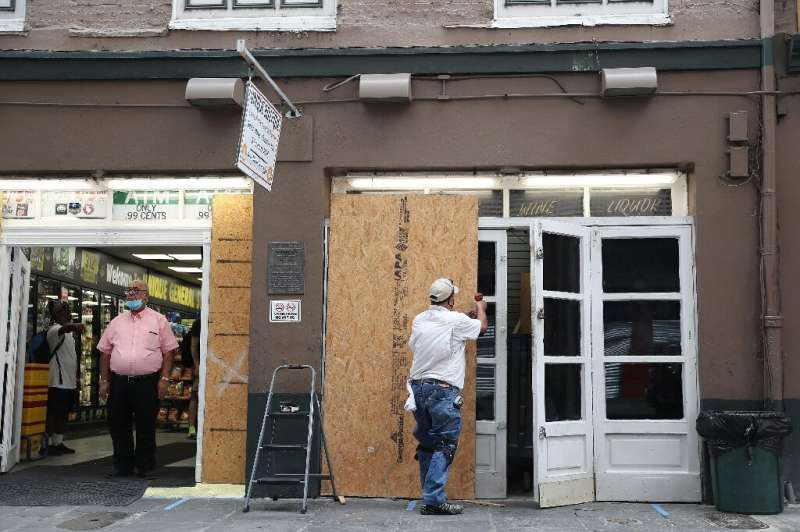 Luis Sanabria puts plywood over the windows of a business in the historic French Quarter before the possible arrival of Hurrican