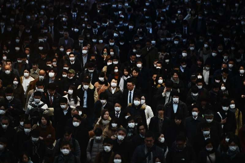 Mask-clad commuters make their way to work during morning rush hour at the Shinagawa train station in Tokyo