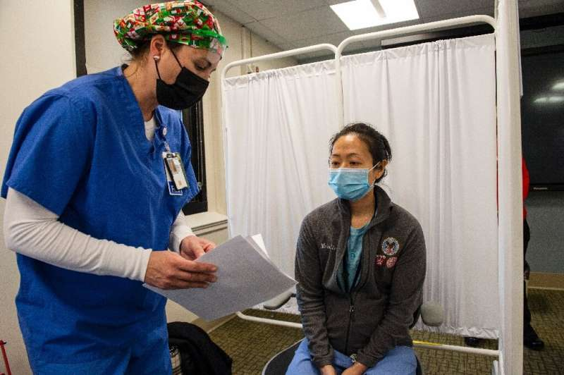 Nurse Renee Langone speaks to US Air Force doctor Pei-Chun McGregor before administering the Moderna Covid-19 vaccine at the Wes